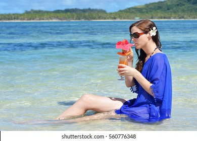 Tourist woman drinks a tropical cocktail in the waters of a resort on an island in Fiji. Travel holiday vacation concept. Real people copy space