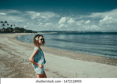 Tourist woman enjoy vacation on Kuta beach. Bali traveller. Explore beautiful Indonesia landscape. People travel. Tourism concept. Flower in wavy hair. Tropical resort. Copy space. Blue sky background