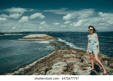 Tourist woman enjoy vacation on Kuta beach. Bali traveller. Explore beautiful Indonesia landscape. People travel. Tourism concept. Girl slim figure. Tropical resort. Copy space. Blue sky background