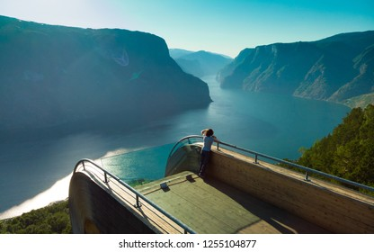 Tourist woman enjoying fjord view Aurlandsfjord landscape from Stegastein viewing point. Norway Scandinavia. National tourist route Aurlandsfjellet.
