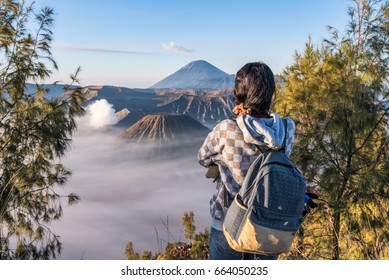 A tourist woman enjoying to fog covered Bromo mountain valley at sunrise.
