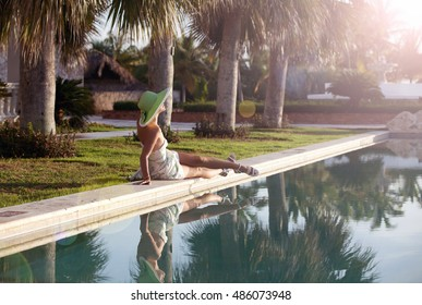 Tourist woman enjoying sunset at the poolside. Relaxation, serenity, mindfulness and stress free concepts.