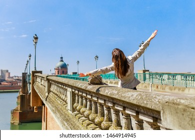 Tourist woman in French ancient town Toulouse and Garonne river. Toulouse is the capital of Haute Garonne department and Occitanie region, France, South Europe. Famous city and tourist destionation.