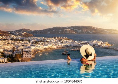 A tourist woman with a glas of wine in a swiming pool enjoys the view over the town of Mykonos island, Greece, during summer sunset time - Shutterstock ID 1904844076