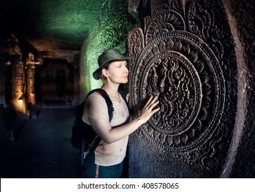 Tourist woman in green hat touching ancient carved mandala at the wall of Ajanta cave near Aurangabad, Maharashtra, India