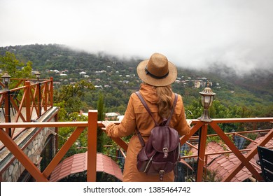 Tourist woman in hat and backpack is looking at foggy hills in Signagi, Georgia