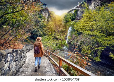 Tourist Woman in Hat going to waterfall in Botanical Garden with autumn trees at overcast cloudy sky in Tbilisi, Georgia