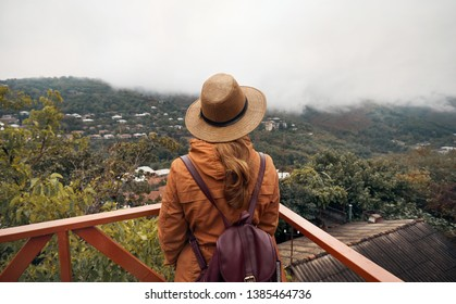 Tourist woman in hat is looking at foggy hills in Signagi, Georgia