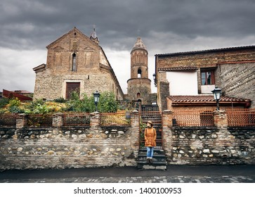 Tourist woman in hat near old church from stone in Signagi, Georgia