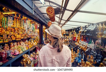 Tourist woman in hat and pink shirt at market with souvenirs in Bangkok, Thailand