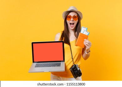 Tourist woman holding laptop pc computer with blank black empty screen passport tickets isolated on yellow orange background. Female traveling abroad to travel on weekends getaway. Air flight concept
