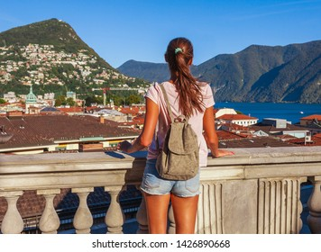 Tourist woman of the lake Lugano, mountains and city Lugano, Ticino canton, Switzerland. Traveler in scenic beautiful Swiss town with luxury villas. Famous tourist destination in South Europe