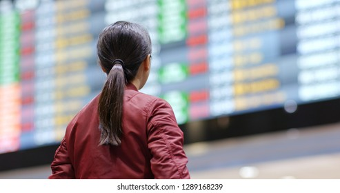 Tourist woman look at the flight number display board in the airport