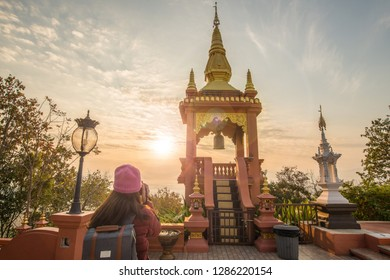 Tourist woman looking to the beautiful sunrise over Wat Phra That Doi Phra Chan one of the most beautiful Buddhist temple on the hills in Lampang province of Thailand.