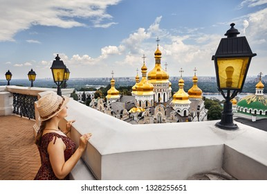 Tourist woman is looking from Bell Tower at Kiev Pechersk Lavra Christian complex. Old historical architecture in Kiev, Ukraine