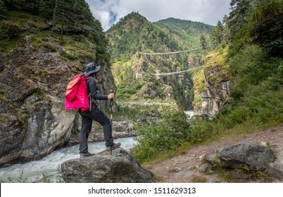 Tourist woman looking to Tenzing-Hillary Suspension Bridge, the bridge build for crossing the river in Sagarmatha national park, Nepal. An iconic memorial bridge during Everest base camp treks.