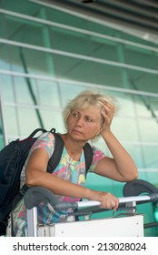 Tourist woman lost in thought at the airport. Vertical photo.