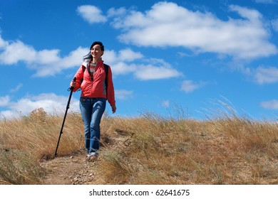 Tourist woman in mountains on the cloudy sky background