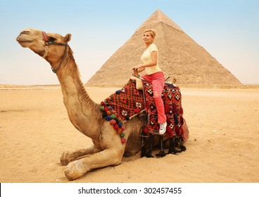 Tourist woman on camel in Giza. Young blonde near Pyramid of Khafre, Egypt