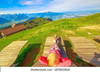 Tourist woman on deckchair relaxing from a top of Rigi-Kulm, Mount Rigi. Tourist enjoys outdoor activities of Rigi Railways, the queen of mountains, one of most popular excursions in Switzerland.