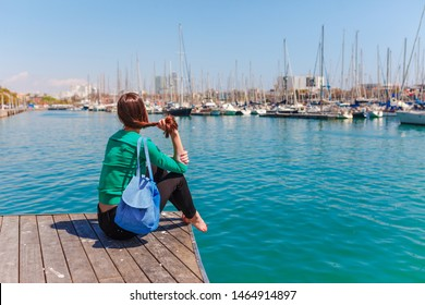 Tourist woman in the port of Barcelona, Catalonia, Spain. Scenic seascape of marina and sailboats yachts. Public promenade and famous tourist destination near La Ramblaa street