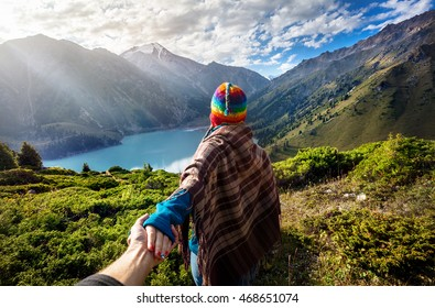 Tourist woman in rainbow hat and brown poncho holding man by hand and going to the lake in the mountains