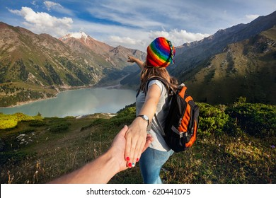 Tourist woman in rainbow hat and brown poncho holding man by hand and pointing to the lake in the mountains