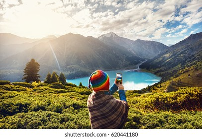 Tourist woman in rainbow hat and brown poncho taking picture with her smartphone  in beautiful Mountain Lake in Kazakhstan