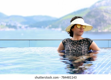 A tourist woman relaxing in the infinity pool of her hotel. She wears a black swimsuit, beach hat with visor and mirrored sunglasses. Fashion.