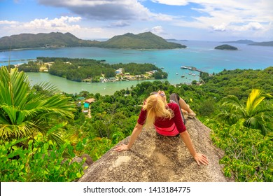 Tourist woman relaxing at lookout of Praslin after trekking inside Reserve of Fond Ferdinand. Scenic view from top view of Praslin on Bay of St. Anne. Amazing views of Seychelles and Indian Ocean.