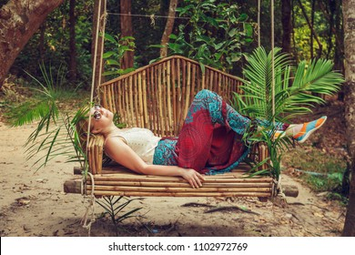 Tourist woman relaxing on a swing in the rainforest. Phnom Kulen, Cambodia.