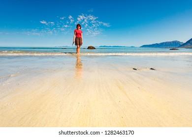Tourist woman relaxing walking on sea shore. Coast of Gimsoya island, Gimsoysand sandy beach in summer. Nordland county, Lofoten archipelago Norway.