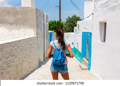 Tourist woman in scenic old town Archangelos on Rhodes island, Dodecanese, Greece. Beautiful picturesque ancient white houses with flowers. Famous tourist destination in South Europe