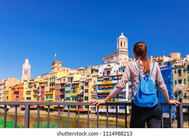 Tourist woman see on colorful red and yellow houses and bridge river Onyar in Girona, Catalonia, Spain. Scenic ancient town. Famous tourist resort destination perfect place for holiday and vacation