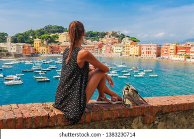 Tourist woman in Sestri Levante, Liguria, Italy. Scenic fishing village with traditional houses and clear blue water. Summer vacation rich resort with picturesque harbour and nice sand beach