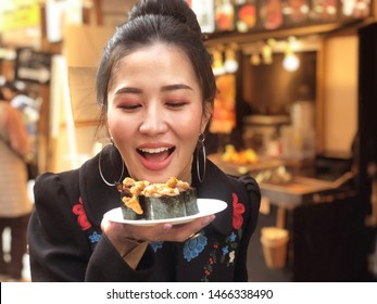 Tourist woman showing beef sushi most popular delicious food in street food tsukiji fish market,  Japan