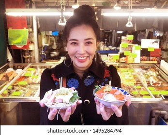 Tourist woman showing salmon sashimi most popular delicious food in street food tsukiji fish market, Japan