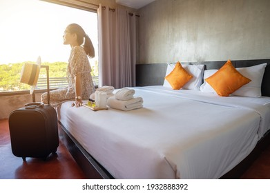 Tourist woman sitting on bed nearly window, looking to beautiful view with her luggage in hotel bedroom after check-in. Conceptual of travel and accommodation. - Shutterstock ID 1932888392