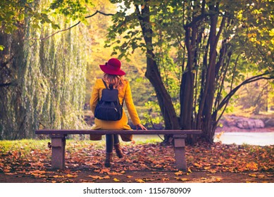 Tourist woman sitting on bench in public park at autumn. Girl wearing yellow coat and red hat relax in nature
