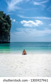 A tourist woman sitting on white-yellow sand beach on the island at the sea of Thailand on some holiday weekend.