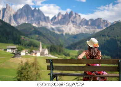 Tourist Woman sitting on wooden bench relaxing her holiday travel to Dolomites in Italy. she wearing straw hat with flower. Looking to beautiful mountain peaks and the church of Santa Maddalena