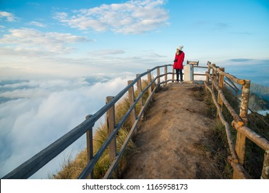Tourist woman standing and looking view on the highest peak of Phu Chi Dao mountain in Chiang Rai province of Thailand. (The Thai language on the wooden sign post is the name of this place)