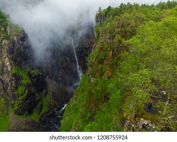 Tourist woman standing on cliff at Voringsfossen waterfall. Mabodalen canyon Norway. National tourist Hardangervidda route, Eidfjord sightseeing tour.