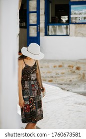 A tourist woman staying in the shade of a old building. Tourist walking in Old town Hersonissos.