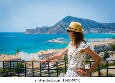 Tourist woman with straw sunhat looking to the mediterranean sea and enjoying the blue and scenic seascape in Altea, Alicante, Spain