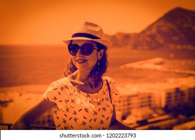 Tourist woman with straw sunhat looking to the mediterranean sea and enjoying the scenic seascape in Altea, Alicante, Spain. The Duotone effect - orange and purple