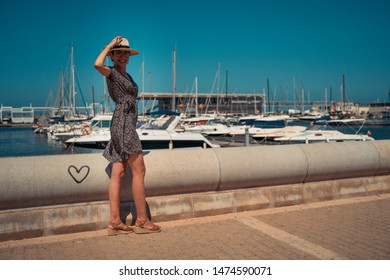 Tourist woman with straw sunhat looking to the mediterranean sea and enjoying the blue and scenic Denia marina Port , Alicante, Spain. Teal and orange style.