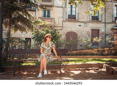 Tourist woman with a straw sunhat sitting on a bench in the medieval town of Solsona