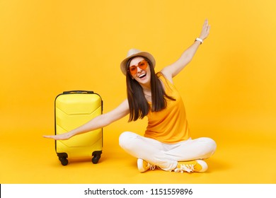 Tourist woman in summer clothes, hat sit at suitcase crossed legs spreading hands as in flight isolated on yellow orange background. Passenger traveling abroad on weekend getaway. Air journey concept