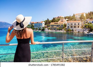 A tourist woman with sunhat looks at the beautiful village of Fiscardo on the island of Kefalonia, Greece, during her summer vacation time
